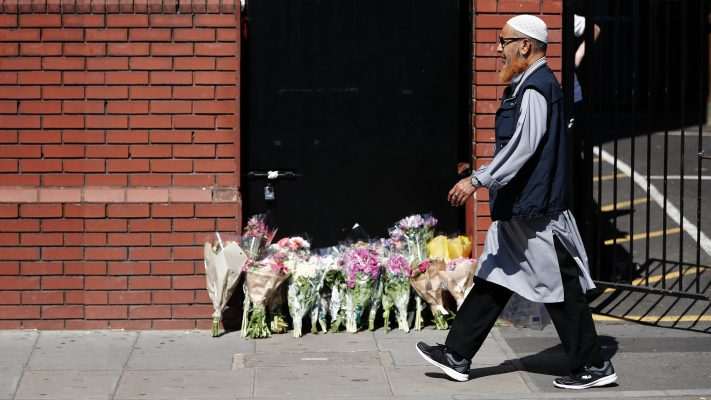 A man walks past floral tributes outside Finsbury Park Mosque in the Finsbury Park area of north London, on June 19, 2017, near to where a vehicle was driven into pedestrians. (Tolga Akmen/AFP/Getty Images)