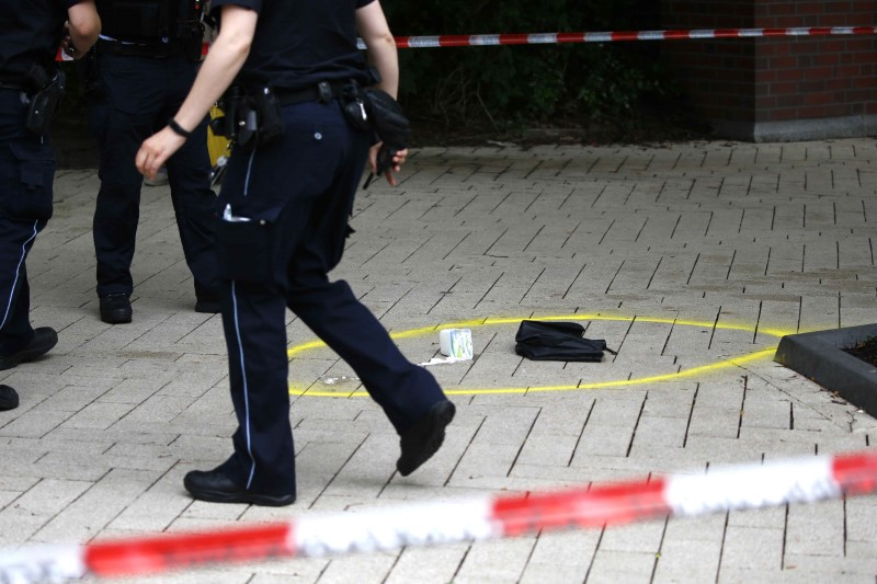 A police officer walks past crime scene after a knife attack in a supermarket in Hamburg, Germany, July 28, 2017. (REUTERS/Morris Mac Matzen)
