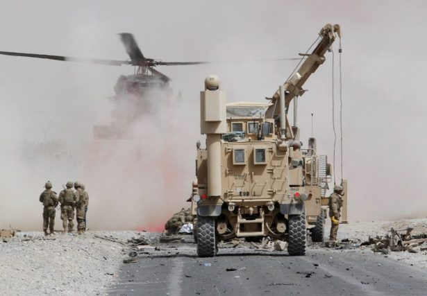U.S. troops assess the damage to an armoured vehicle of NATO-led military coalition