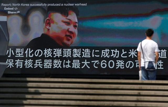 A passerby walks past a street monitor showing news of North Korea's fresh threat in Tokyo, Japan, August 9, 2017. (REUTERS/Issei Kato)