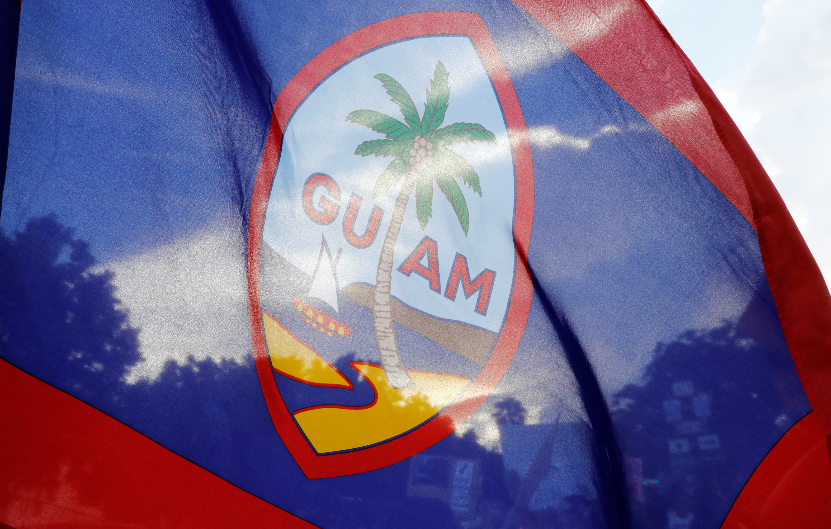 Local residents display a Guam flag during a peace rally at Chief Quipuha Park, on the island of Guam, a U.S. Pacific Territory, August 14, 2017. (REUTERS/Erik De Castro)