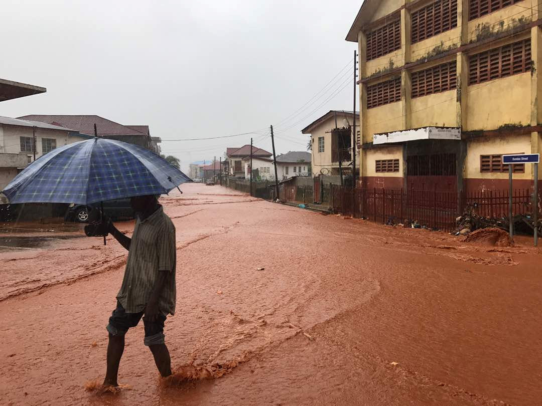 A man walks under umbrella in water covered street in Freetown, Sierra Leone August 14, 2017 in this picture obtained from social media. Instagram/dawncharris via REUTERS