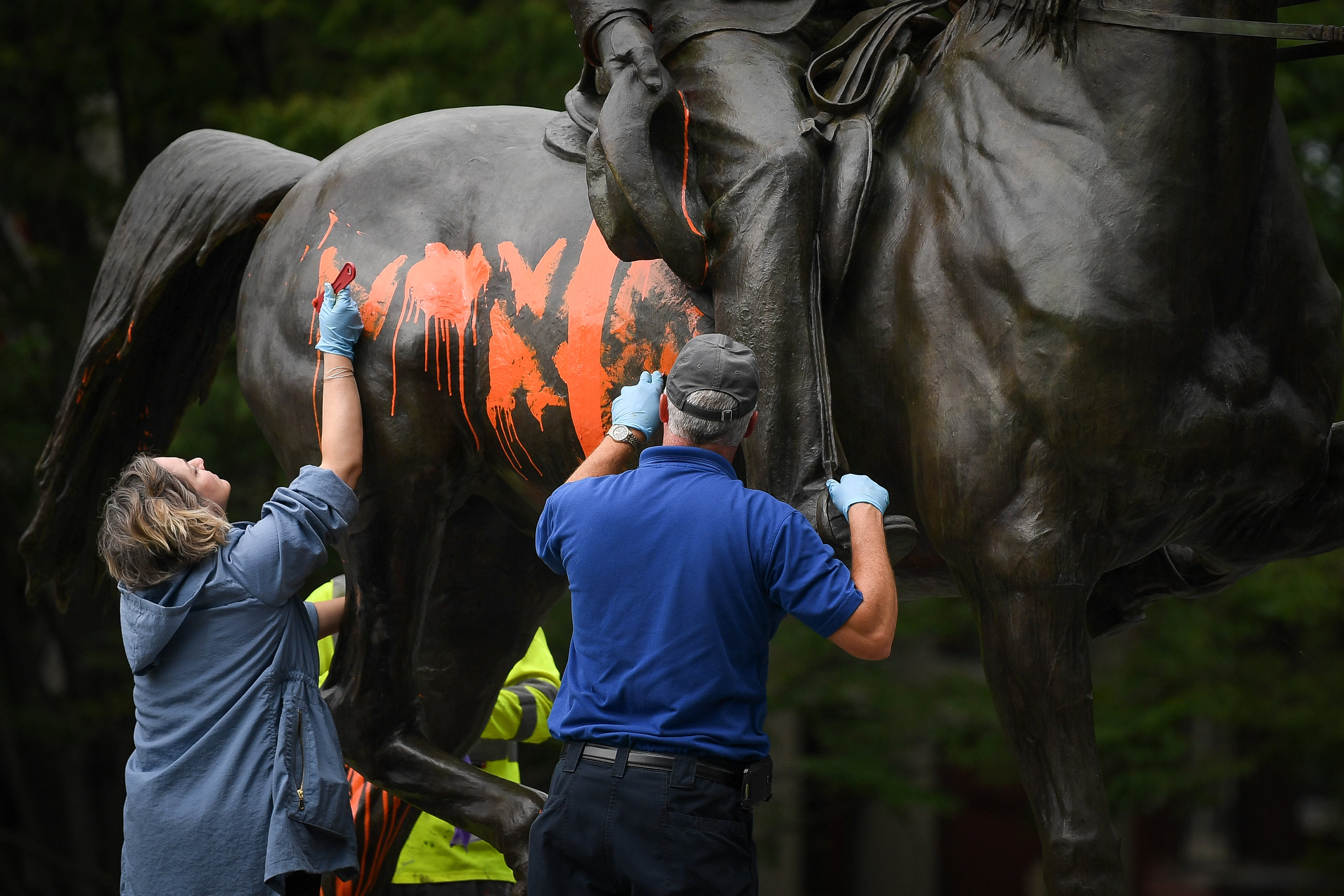 Municipal workers attempt to remove paint from a monument dedicated to Confederate soldier John B. Castleman that was vandalized late Saturday night in Louisville, Kentucky, U.S., August 14, 2017. (REUTERS/Bryan Woolston)