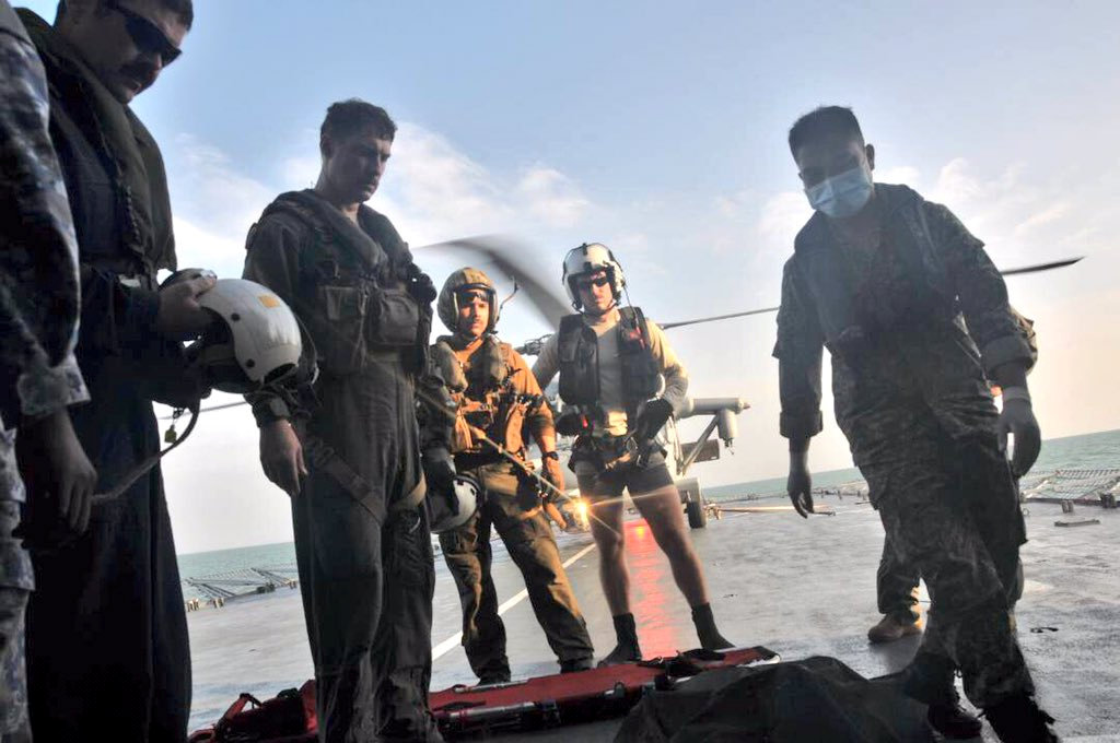 U.S. Navy personnel prepare to carry a body onto U.S. Navy helicopter from USS America during a search and rescue operation for survivors of the USS John S. McCain ship collision in Malaysian waters in this handout photo distributed August 23, 2017. Royal Malaysian Navy Handout via REUTERS