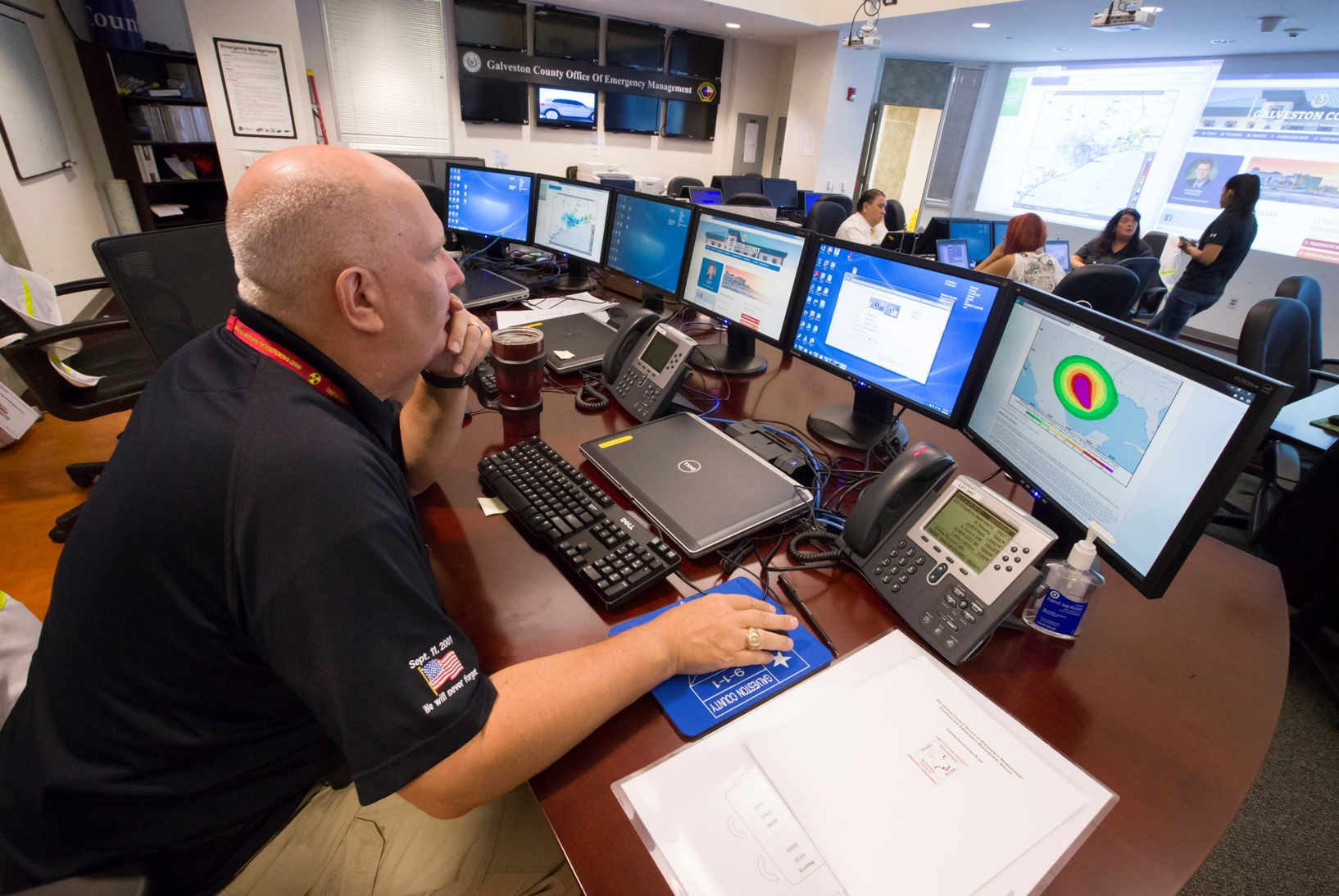 Michael Lambert, the emergency operations center controller at the Galveston County Office of Emergency Management, looks at a bank of monitors in center in Dickinson, Texas, Thursday, Aug. 24, 2017. (Stuart Villanueva/The Galveston County Daily News via AP)