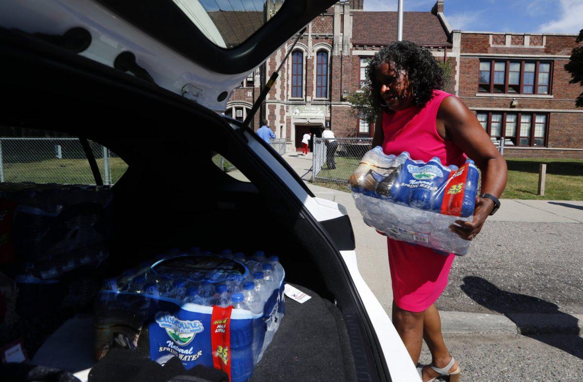 Teacher helps carry bottled water