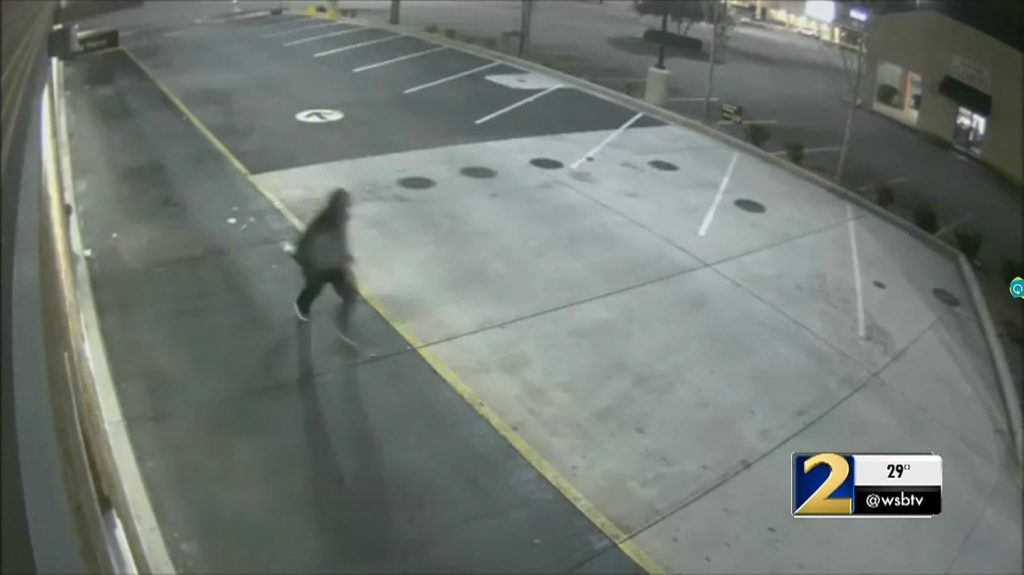 The robber runs across the parking lot and towards a nearby residential community. (Screenshot—WSB-TV)