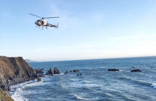 A helicopter hovers at the scene of the crash