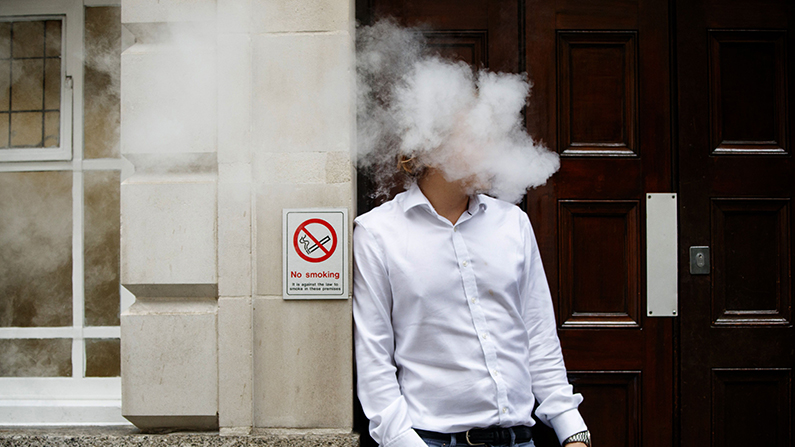 Vapors engulf the head of a man using a vape-pen during his lunch break in central London on August 9, 2017. (Tolga Akmen/AFP/Getty Images)