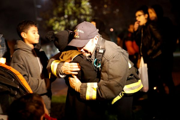 A firefighter embraces a child during a vigil for the victims of the fatal warehouse fire.