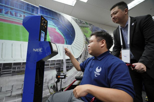 A staff demonstrates a new face recognition system used for the Tokyo 2020 Olympic and Paralympic Games during a press conference in Tokyo on Aug. 7, 2018. (AP Photo/Eugene Hoshiko)