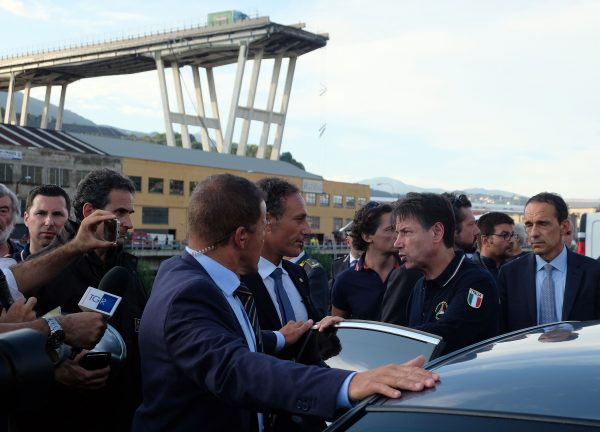 Italian Prime Minister Giuseppe Conte (2ndR) visits the site where a section of the Morandi motorway bridge collapsed in Genoa on Aug. 14, 2018.