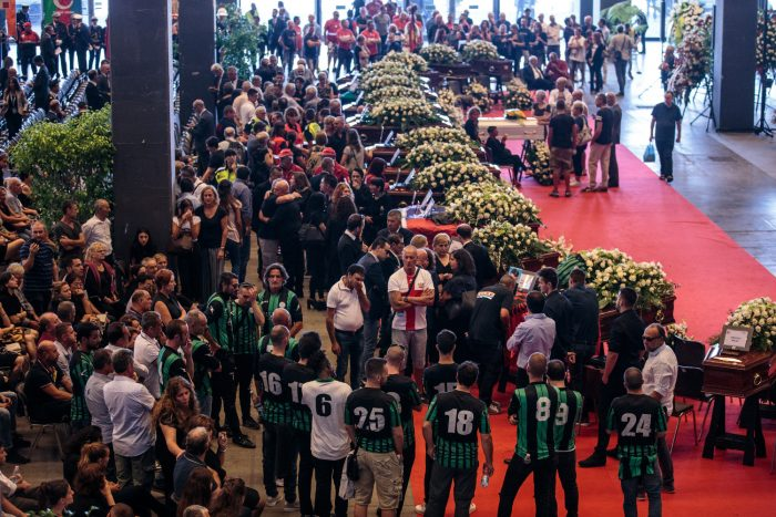Relatives mourn by coffins of victims