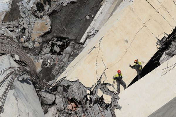 Italian rescuers climb onto the rubble of the collapsed Morandi motorway bridge searching for victims and survivors in the northern port city of Genoa on Aug. 14, 2018.