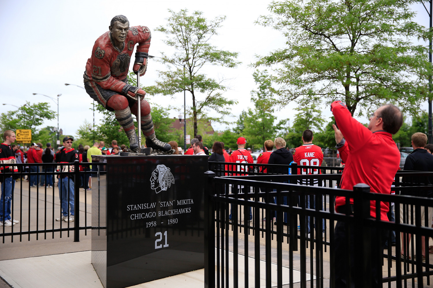 A fan takes a photo of a statue of Blackhawk hockey legend Stan Mikita prior to Game Two of the Western Conference Final during the 2013 NHL Stanley Cup Playoffs at United Center on June 2, 2013 in Chicago, Illinois. (Jamie Squire/Getty Images)