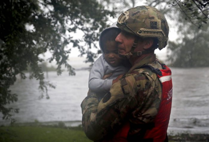 Rescue team member carries a child to safety
