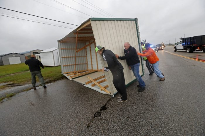 People move a metal structure from the road