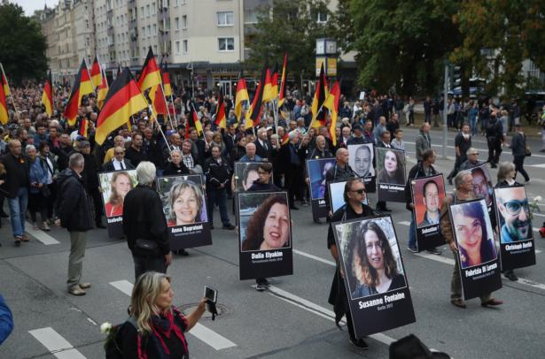 Demonstrators carry German flags