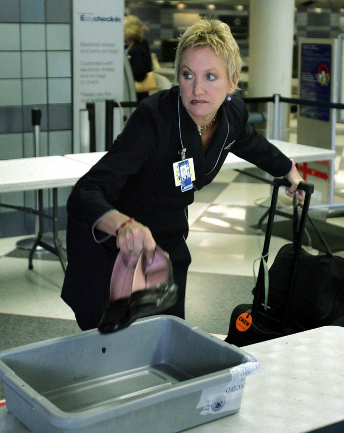 A flight attendant drops her shoes into a plastic tray