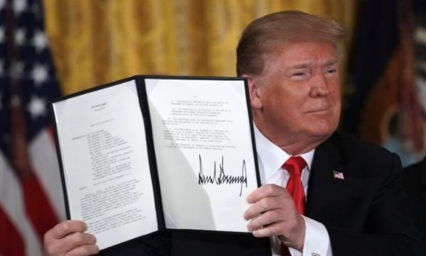 President Donald Trump holds up an executive order for the creation of a Space Force, during a meeting of the National Space Council at the East Room of the White House June 18, 2018, in Washington.