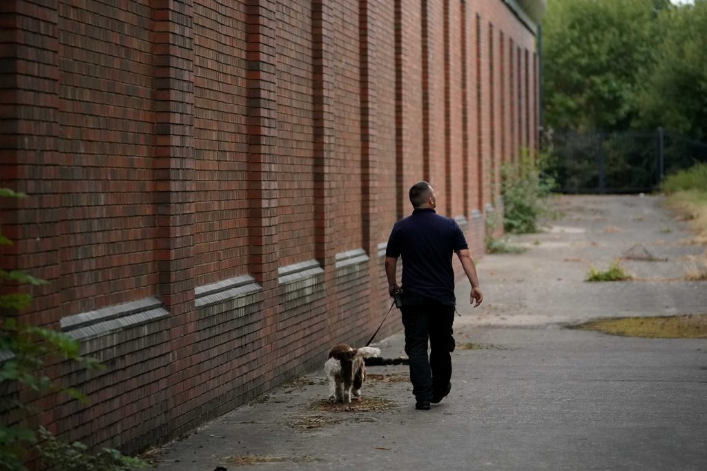 A drug search dog and officer patrol the perimeter of Birmingham Prison
