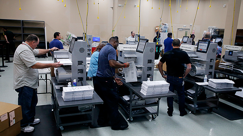 Elections staff load ballots into machines