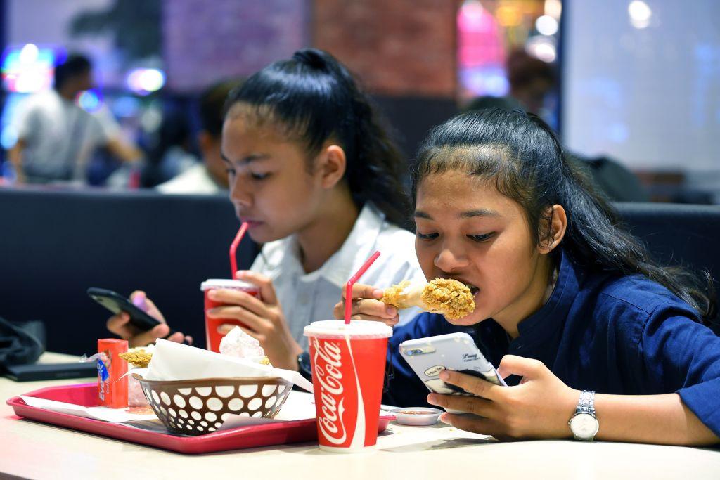 Teens use phones at restaurant