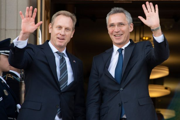 Acting Secretary of Defense Patrick Shanahan (L) waves as NATO Secretary General Jens Stoltenberg