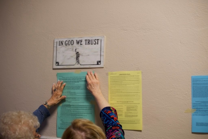 Các quan chức bầu cử gắn thông báo bỏ phiếu lên tường, bên dưới tấm biển ghi 'IN GOD WE TRUST, tại Văn phòng chính quyền thành phố ở Hazleton, Pennsylvania vào ngày 15/5/2018. (Ảnh: Mark Makela/Getty Images)