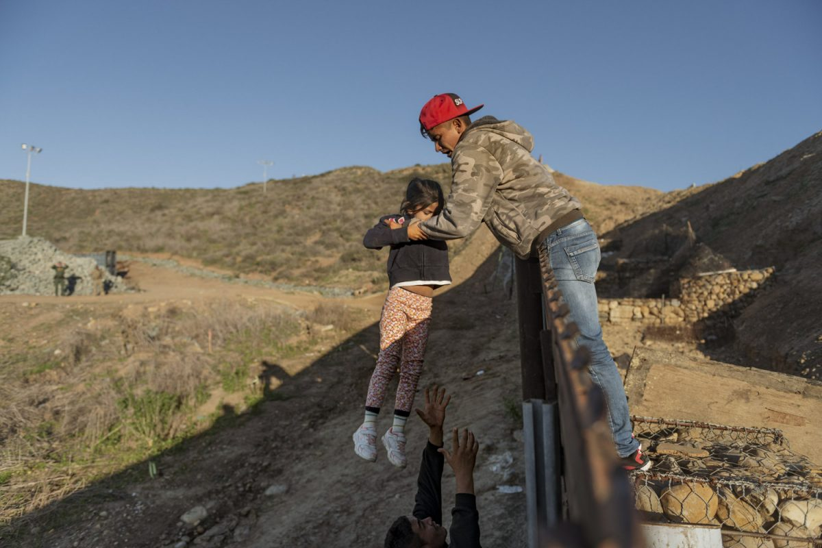 A migrant from Honduras passes a child to her father after he jumped the border fence