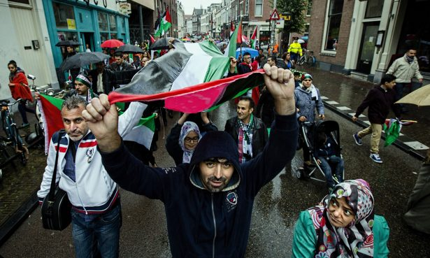 People hold a giant Palestinian flag during a demonstration