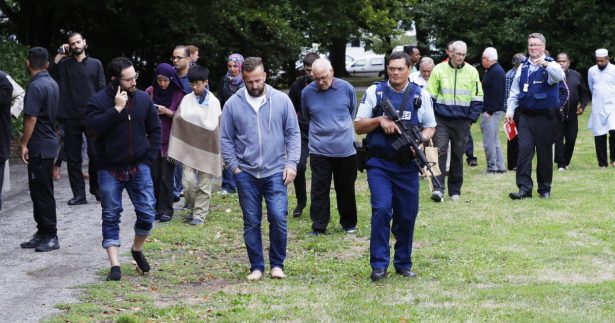Police escort witnesses away from a mosque in central Christchurch, New Zealand