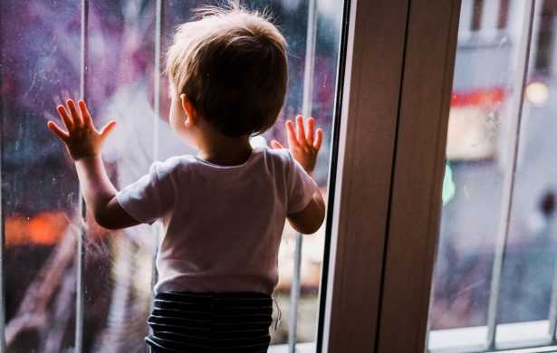 Toddler boy gazes out of window