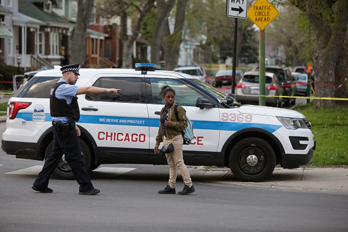 A Chicago Police officer redirects a young woman back around the yellow crime tape