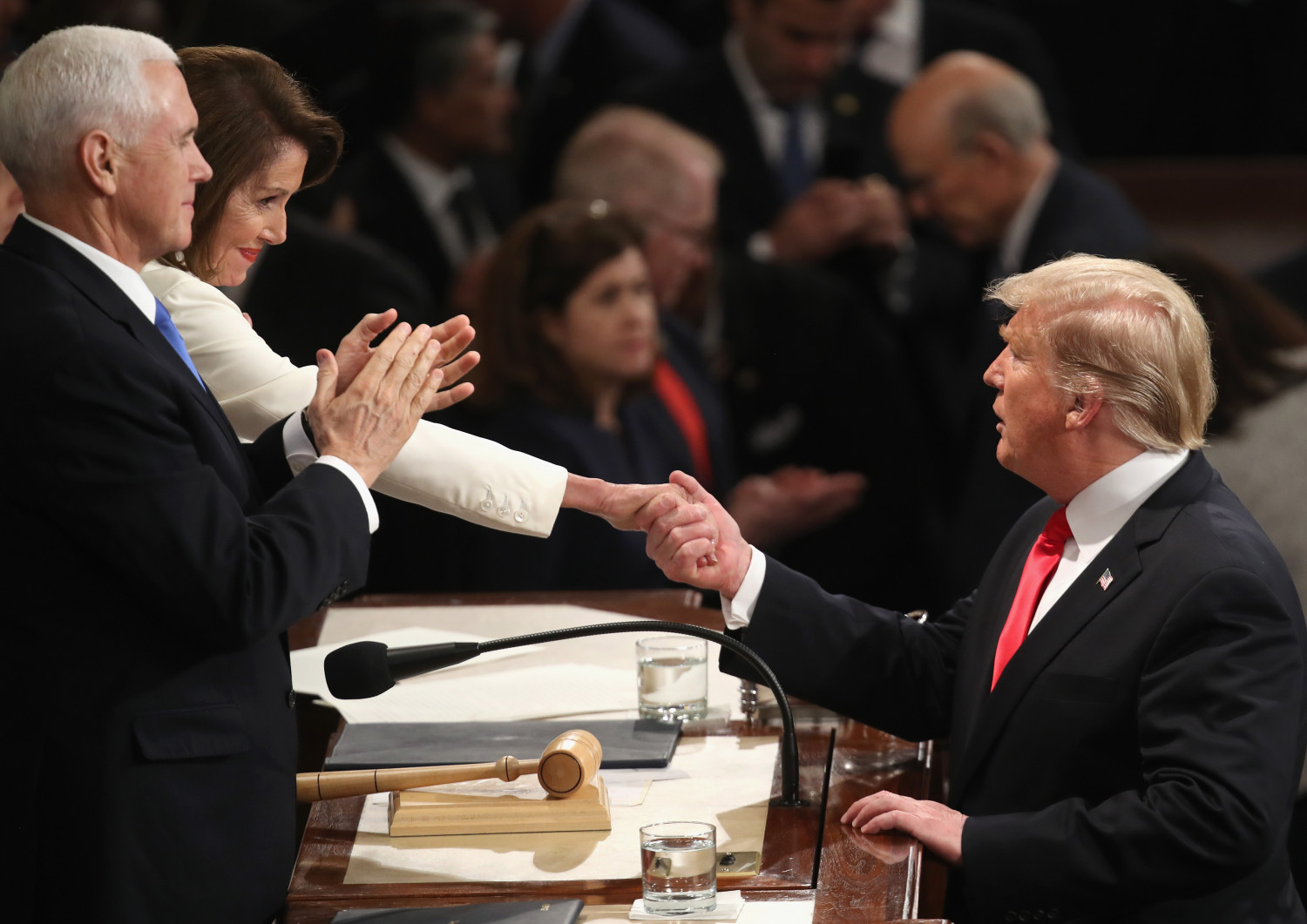 President Donald Trump shakes hands with Speaker Nancy Pelosi, with Vice President Mike Pence