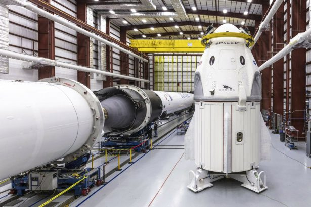 SpaceX's Crew Dragon spacecraft and Falcon 9 rocket are positioned inside the company's hangar at Launch Complex 39A