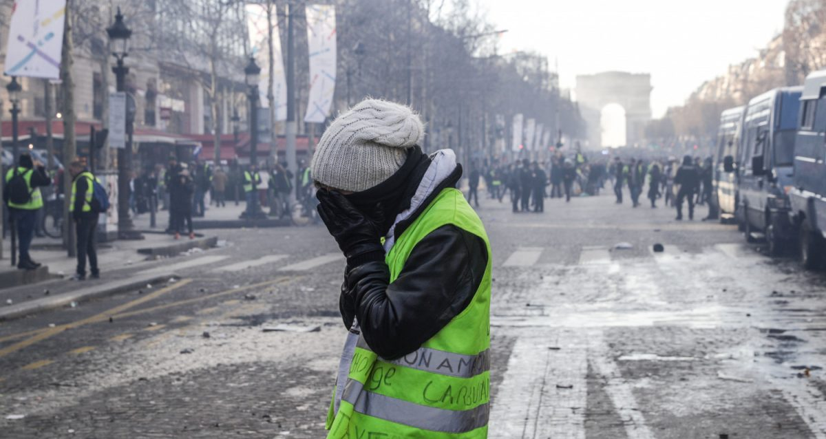 A Yellow Vest protesters holds his face in his hands during clashes between riot police forces and Yellow Vest protesters