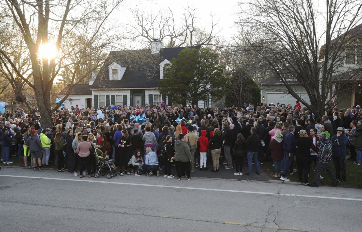 "Mourners gather outside the home of 5-year-old Andrew ""AJ"" Freund for a vigil Wednesday,"