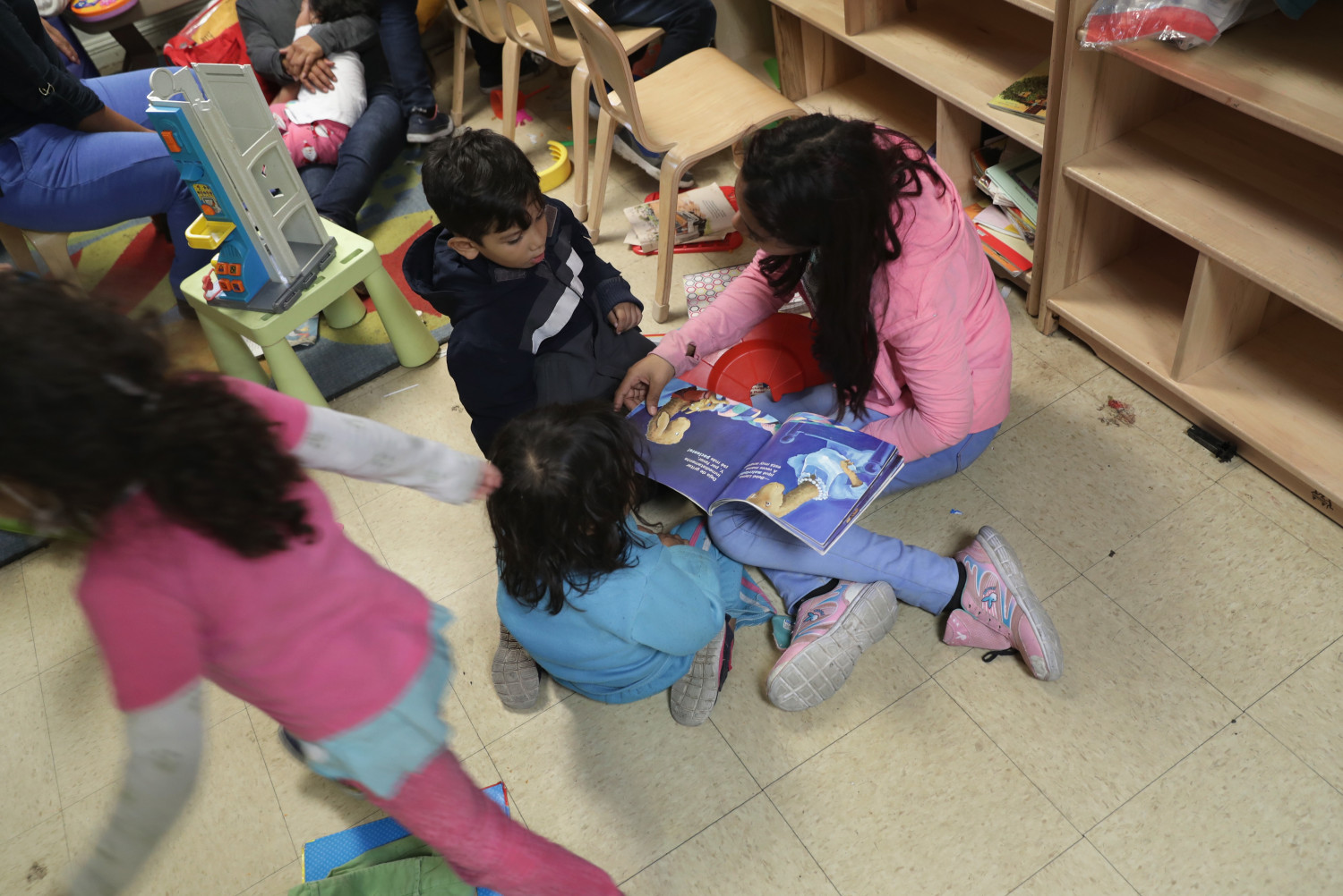 Immigrant children read and play