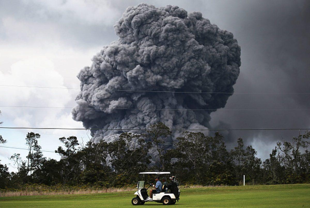 A man drives a golf cart at a golf course as an ash plume rises