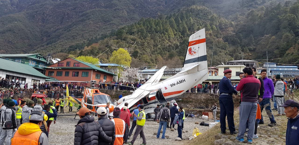 People gather at the site of an airplane crash in Lukla