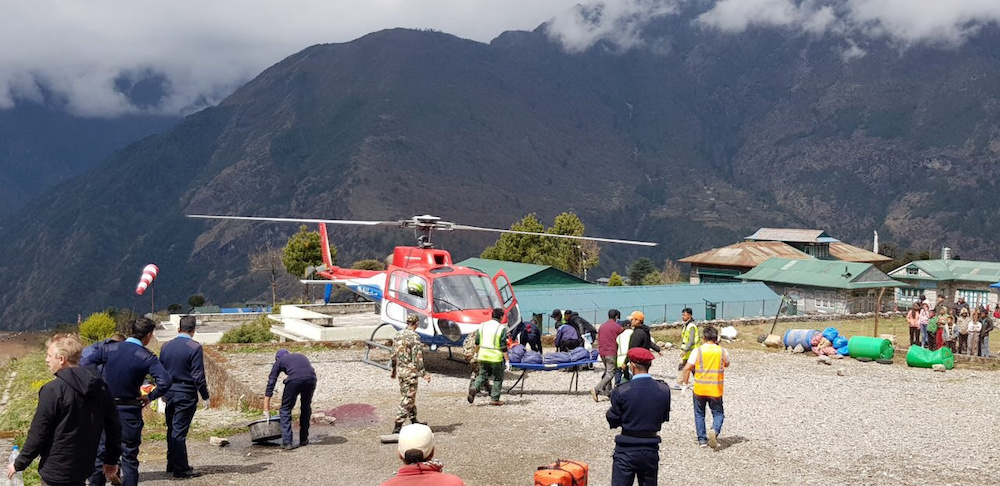 Emergency crews walk at the site of an airplane crash in Lukla