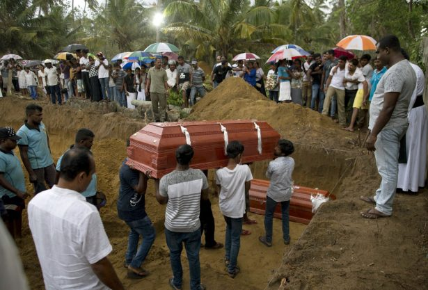 Relatives carry a coffin for burial