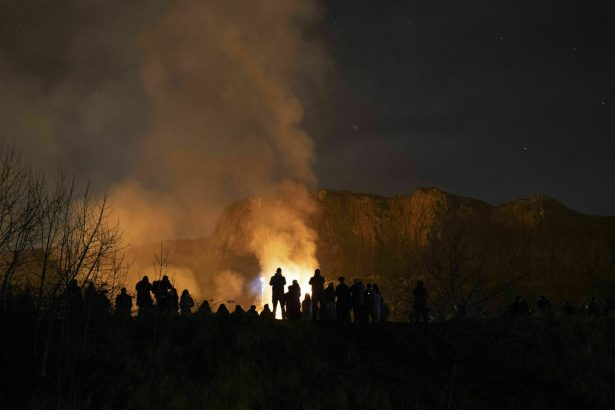 People watch the scene of a gorse fire below Salisbury Crags