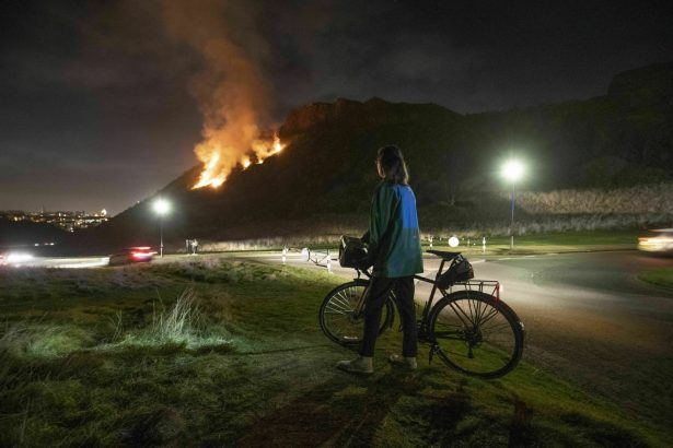 A woman looks at a gorse fire below Salisbury Crags in Holyrood Park,