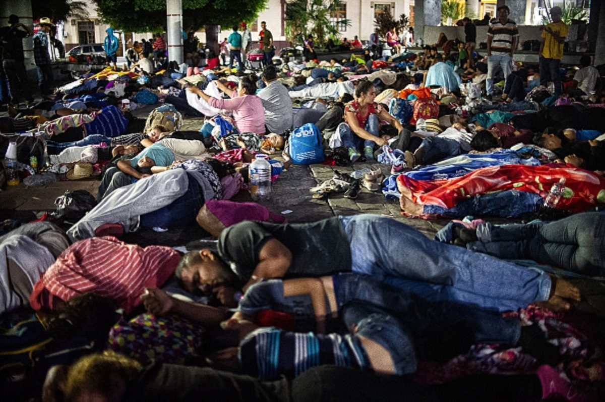 Central American migrants heading in caravan to the US rest during a stop