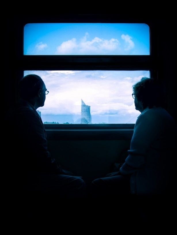 A picture of two people looking out the train window.