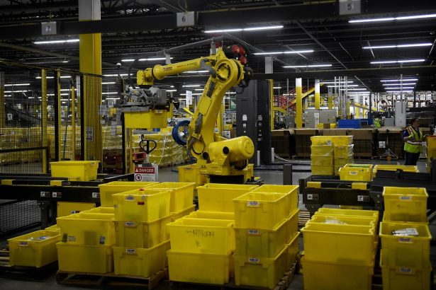 A 6-axis robotic arm picks up sorting containers at the Amazon fulfillment center