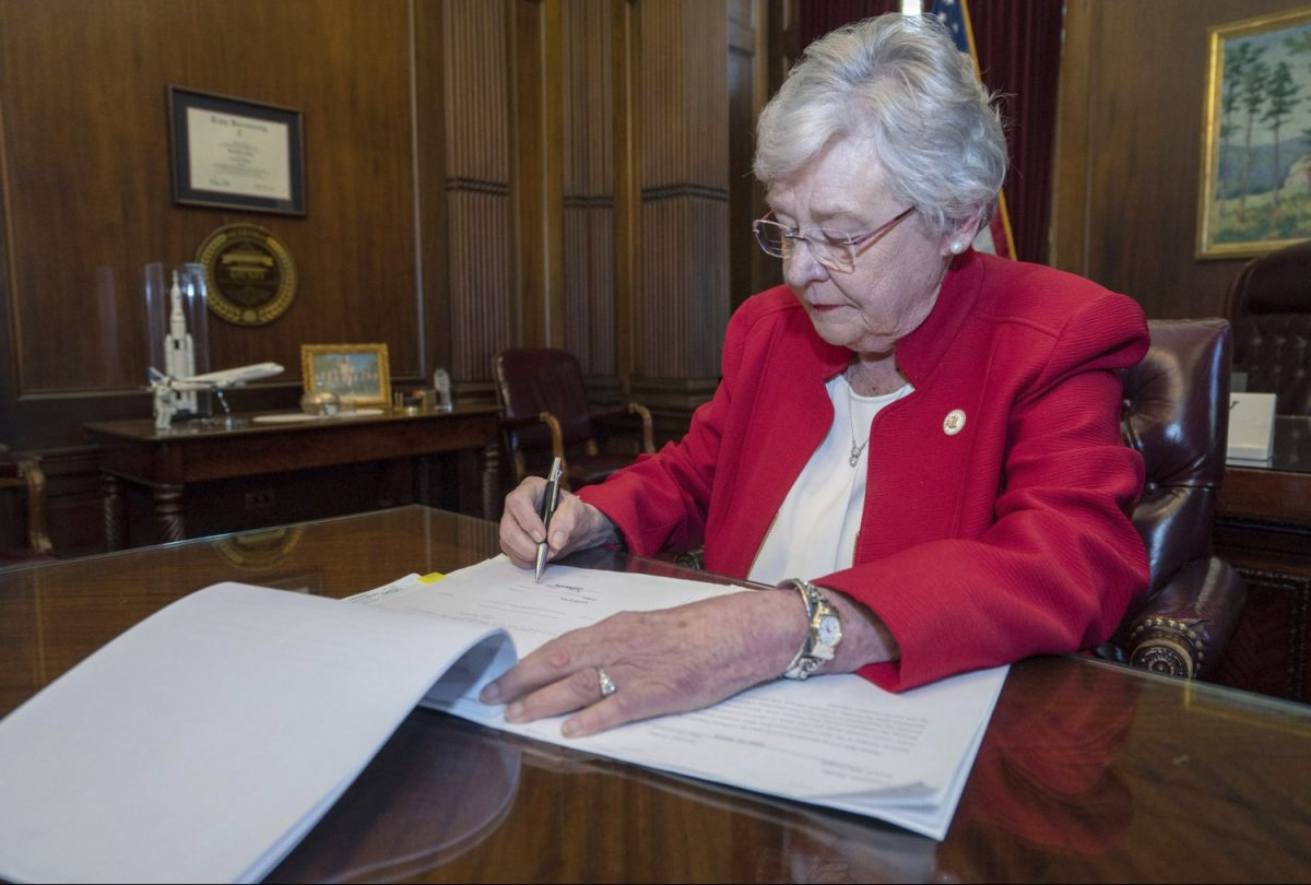 Alabama Gov. Kay Ivey signing a bill