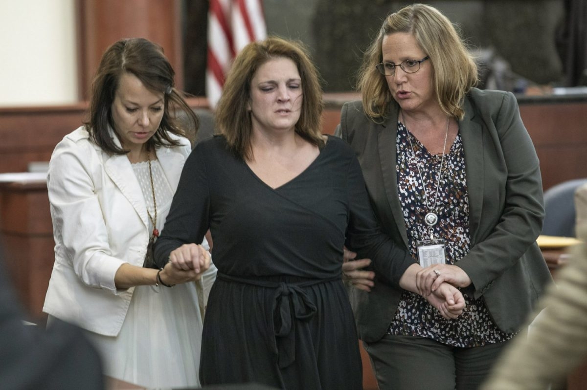 Amber Kyzer is helped out of the courtroom